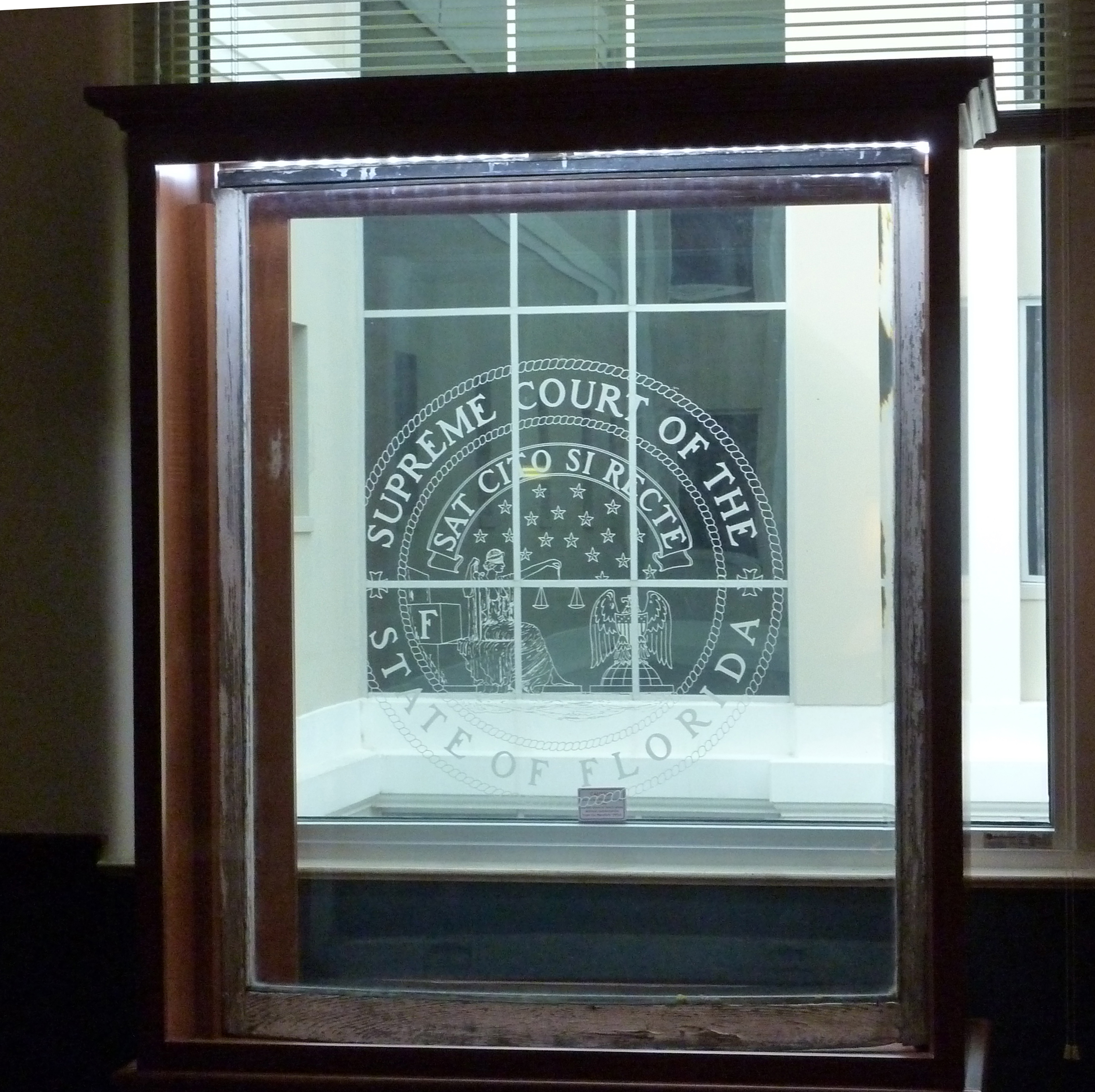 Until 1978, this handsome, curved-glass window etched with the supreme court seal adorned Florida's first Supreme Court Building; the window is now permanently established in the Lawyer's Lounge of the current Supreme Court Building. (BC Schwartz, OSCA)